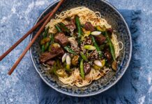 Noodle topped with beef and greens stir fry in a bowl with chopsticks on blue surface.