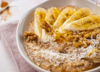 A rice pudding in a white bowl topped with banana slices, walnuts a,d coconut shavings, drizzle of honey