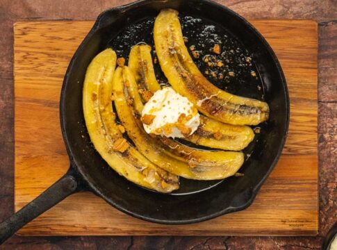 4 long slices of bananas cooked in a black skillet topped with white cream drop, honey drizzle and crumbs
