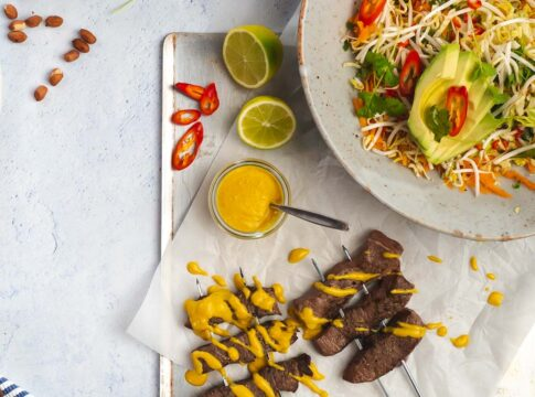 Skewered beef drizzled with yellow sauce on a tray with a bowl of colourful salad, lime halves and chilli.