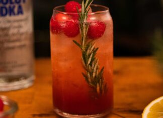 A tall glass of pink drink with rosemary and raspberries on wooden board, lemon half and a bottle of vodka