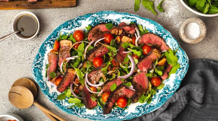 Sliced beef, green leaves, tomatoes and onion salad on oval blue platter surrounded by salad server, pots of salt Pepper
