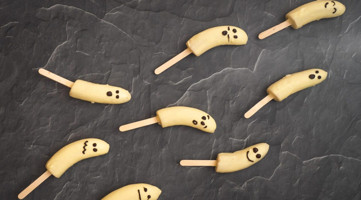 8 white chocolate coated banana halves with faces on popsicle sticks on dark stone board.