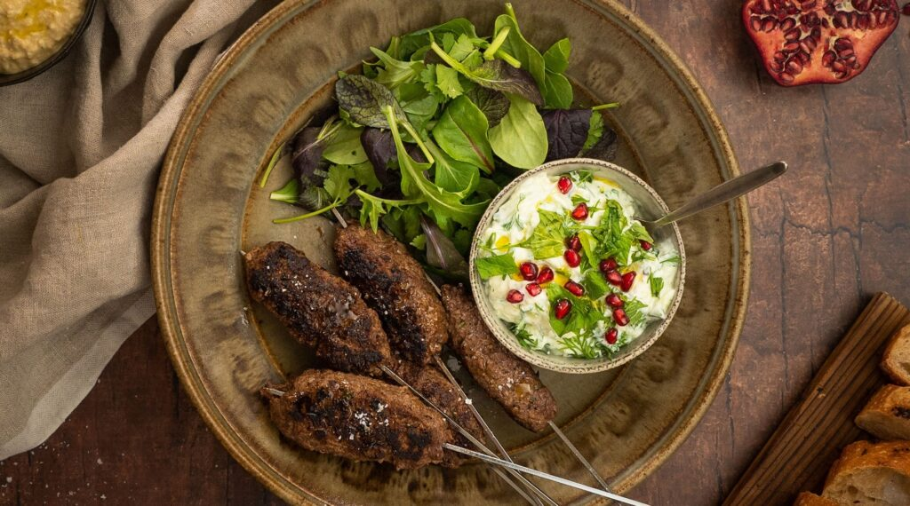 4 meat skewers with greens and a pot of white salad with green and red dots on a brown plate, pomegranate half and bread, pot of hummus.
