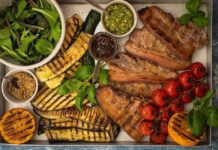 Grilled meat, courgette and aubergine slices, tomatos and orange on a metal tray with a bowl of green salad