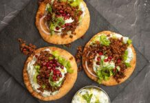 3 round bread topped with white sauce, mince, lettuce and red berries on stone board..