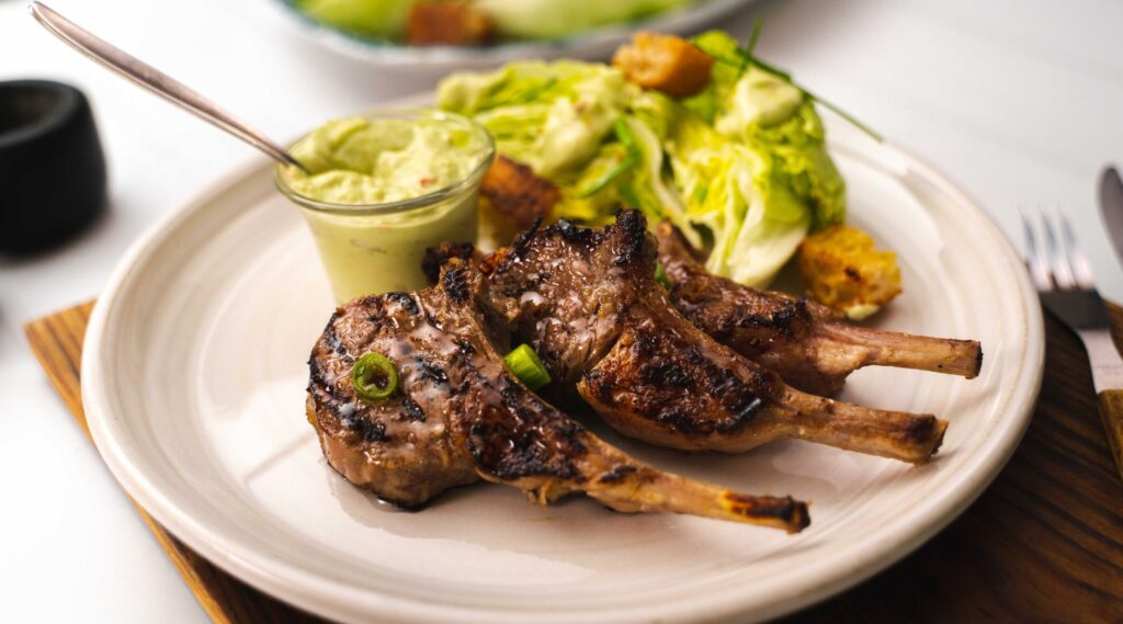 3 lamb chops , lettuce salad and a pot of creamy sauce on a white round plate on brown table mat with fork knife