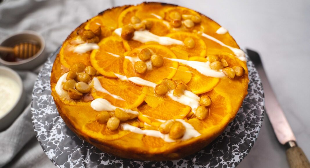 A round orange cake decolated with nouts and white graze on a grey marble board on bench top with a knife