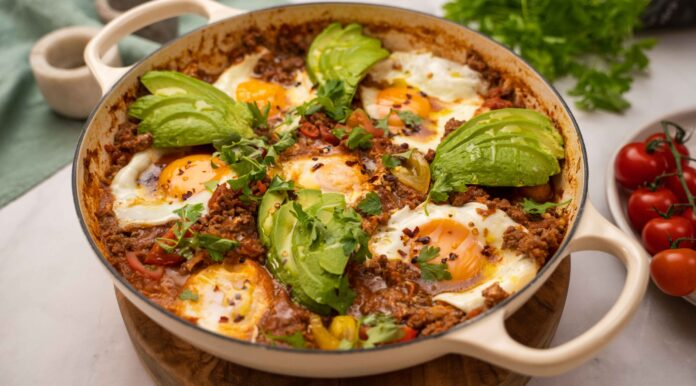 6 eggs cooked in red meaty sauce and avocado slices on top in a white shallow casserole dish