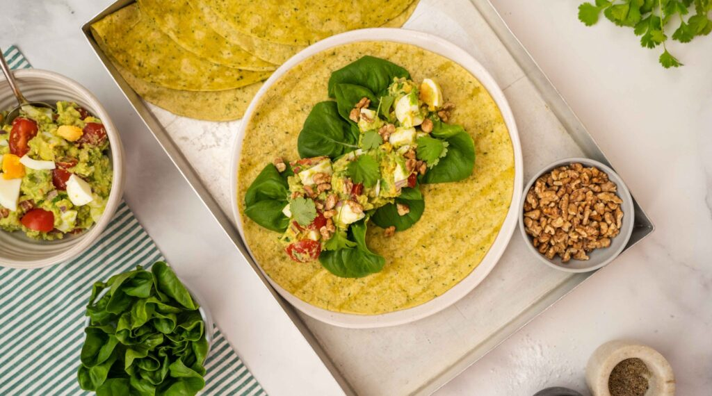Egg salad on a wrap top of lettuce leaves, on a metal tray with bowls of nuts, salad and herbs.