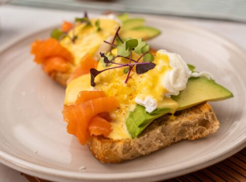 Egg with yellow sauce and herb on top of avocado slices, salmon on bread base on a white plate