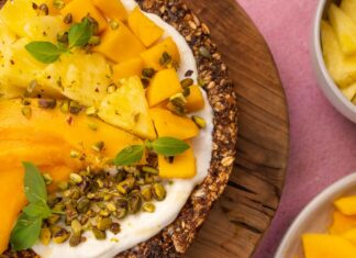 Yellow tropical fruit and green herb on granola disc on wooden board.