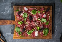 Red meat pieces, green herbs, radish slices scattered on a wooden board on top pf stone slate.