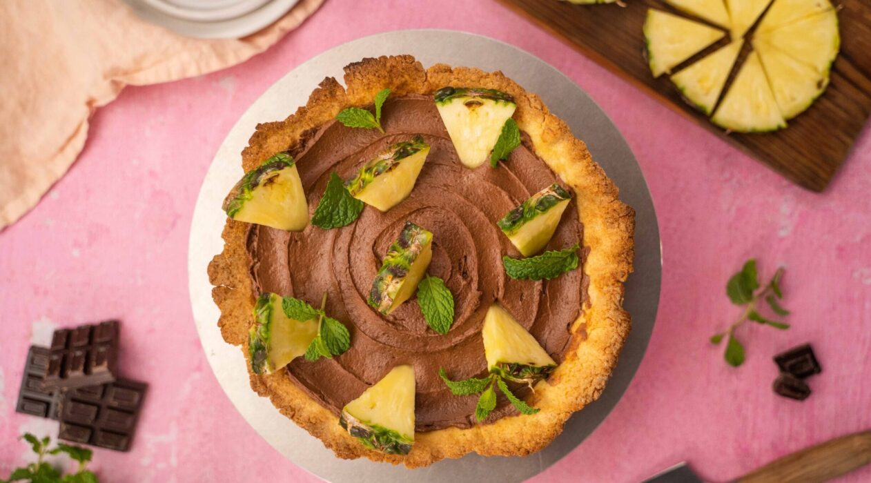 op view of a round chocolate tart with pineapple pieces on pink background with cut pineapple on wooden board, chocolate pieces and plates.