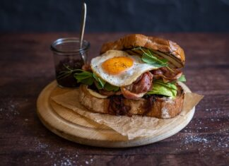 A bacon and egg sandwich on wooden board with a pot of relish
