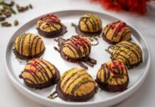 Nine chocolate decorated macaroons on a white round plate and pistachios and red flower in the back