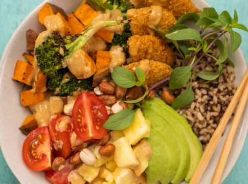 Burger, tomatoes, pineapple, broccoli, kumara, herb and avocado on rice bowl with chopsticks