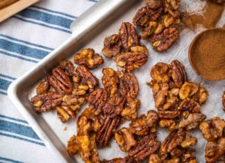 A corner of a rectangle tray with brown nuts, a wooden spoon full of cinnamon powder on green striped cloth, and a tray of cinnamon sticks