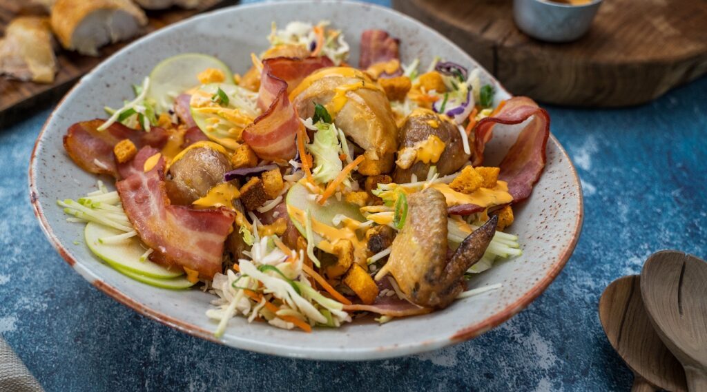 chicken and bacon on top of salad with orange sauce in a large bowl on blue table