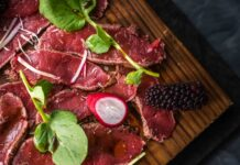 pieces of thin sliced meat on wooden board topped with herbs , radish and blackberry.