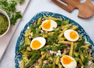 A part of large platter full of penne pasta and asparagus salad in green dressing topped with four halves of hard boiled egg. Salad servers, a pot of pesto sauce and herbs.
