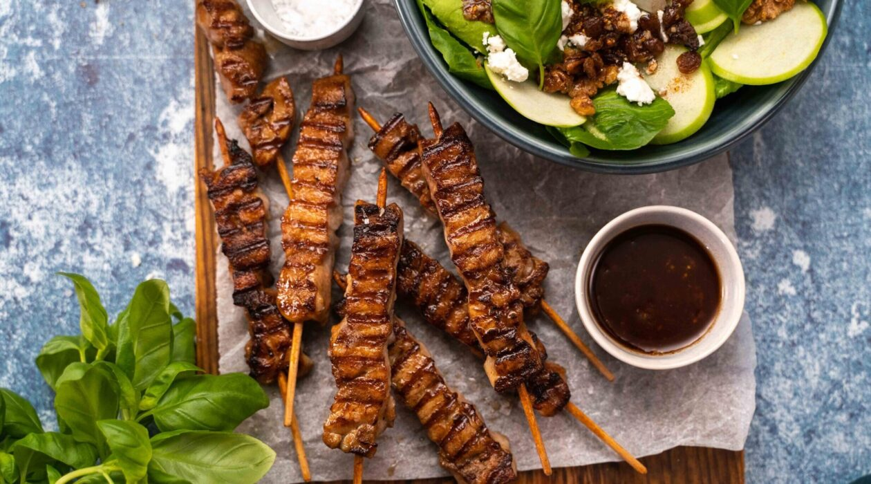 Several grilled meat skewers, a bowl of greenish salad, small bowls of dark sauce and salt, basil on blue background