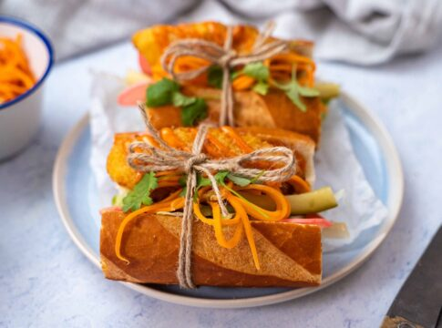 Two pieces of baguette filled with broen, orange and green food each tied with a string on blue plate, small pots of carrots and radish, a pair pf scissors.
