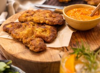 Fried crumbed meat on wodden board with a pot of orange coloured sauce, two glasses of drinks in front