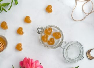 top view of an open jar with four hart shaped sweets inside, more sweets outside, a flower, pot of honey, string and scissors on white bench top