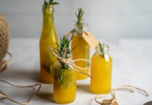Four small bottles full of yellow liquid with rosemary sprigs, strings on white bench top.