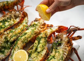 Six cooked crayfish halves with herb on top, a hand squeezing a lemon half and a cut lemon on food.
