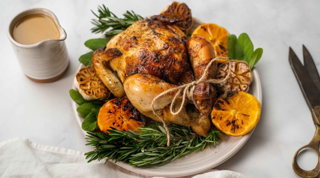 A cooked whole chicken on bed of green herbs with cooked orange halves on white plate and a jug of brown sauce