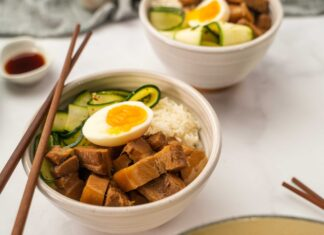 Two bowls of cooked meat , courgettes and boiled egg on rice with chopsticks on a white table with cloth, pot of dark sauce