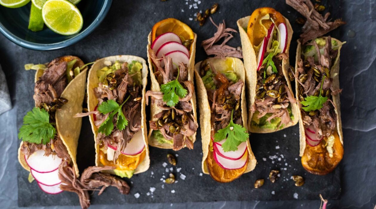 Top view of four taco filled with meat, radish and herb on black slate, a bowl of cut limes . salt flakes scattered.