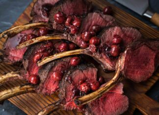 Ten cutlets of pink cooked meat on wooden board topped with red cherries and a knife