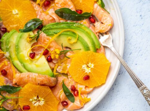 Orange, avocado and salmon slices on a plate topped with red berry, citrus zest and herb with a fork on pale blue table top