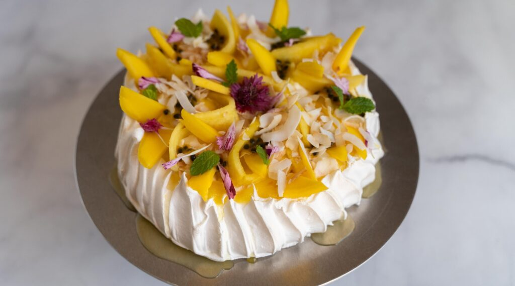 A large white cake topped with yellow fruit, red, white and green foods on a golden plate on marble.