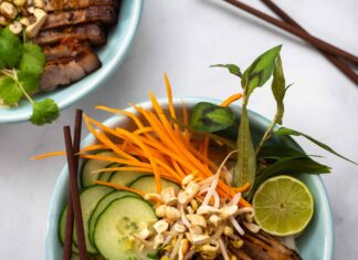 Two bowls full of carrot, cucumber, mint leaves, bean sprouts, pork pieces with chopsticks on white marble.