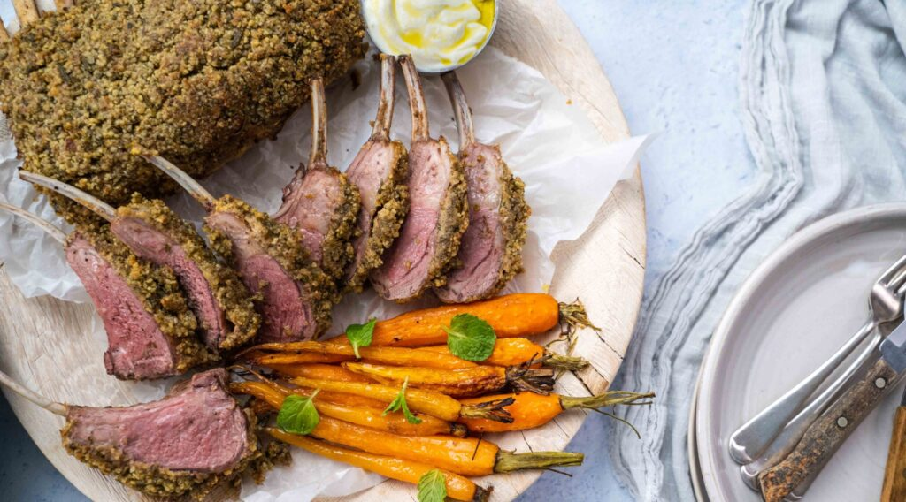 Nut crusted frenched lamb rack pieces on a plate with carrots and pot of white sauce