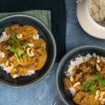 Two black bowl of curry and a white pot of rice on blue table