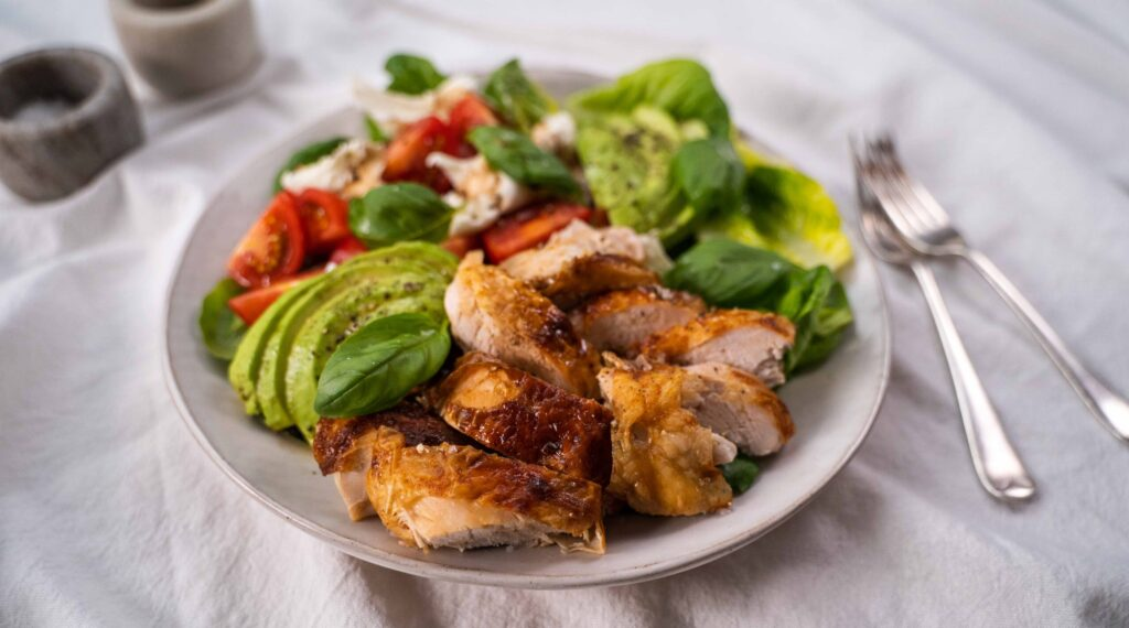 A white bowl of salad consists of chicken pieces, avocado, tomatoes, lettuce with cutlery on white cloth, pots of salt and pepper.