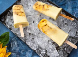 Four creamy coloured popsicles on bed of ice cubes in a tray on blue background with a sunflower.