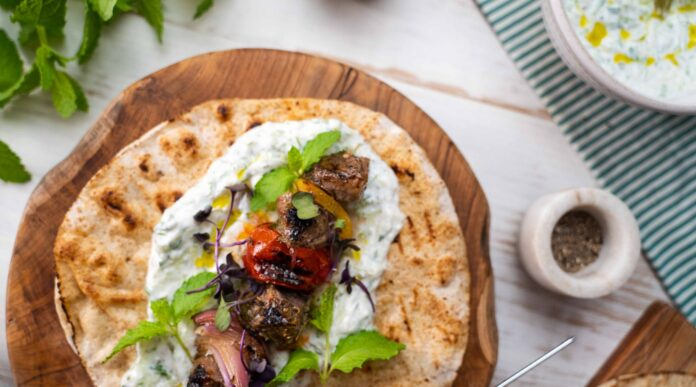 Top view of cooked meat and tomato on top of round flat bread with white sauce, green herbs on a wooden board on white table. A bowl of white sauce, pepper and green herb plant around it.