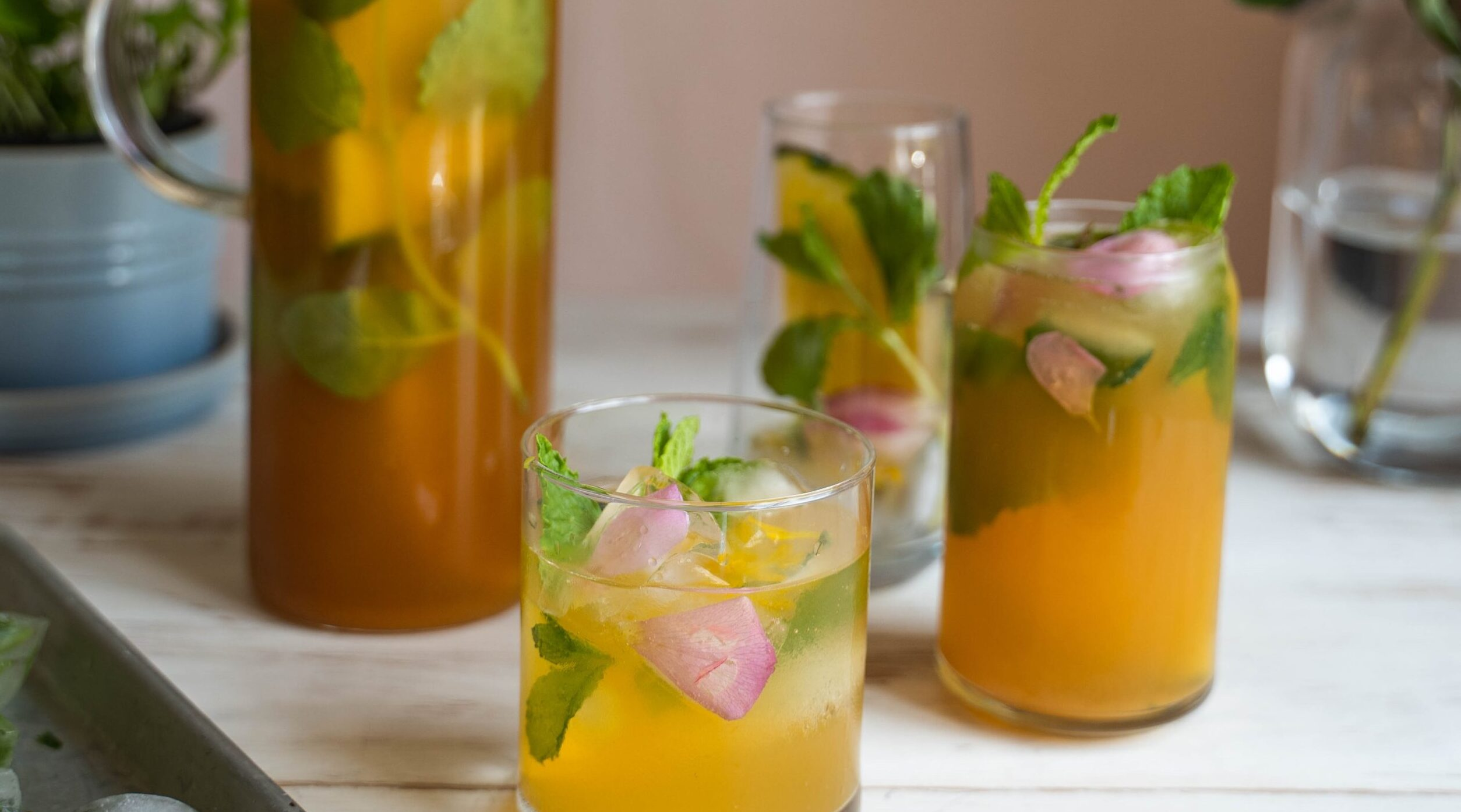 Three tall glasses of yellow drink with ice and herb and a jug of the drink o white table top