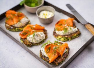 Four brown cakes topped with white sauce, sliced smoked salmon and herb on a tray with two pots of sauce and herb. And a knife on tray edge.