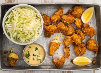 Fried chicken nuggets on tray with lemon wedges, pot of pink sauce and a bowl of shredded cabbege.