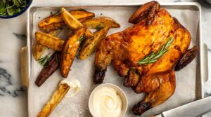 A roast whole chicken topped with rosemary, wedges and a pot of white sauce on a metal tray, and a knife.