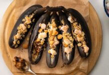 Five blackened bananas topped with pink and brown toppings on wooden board and a bowl of pink and white sweets