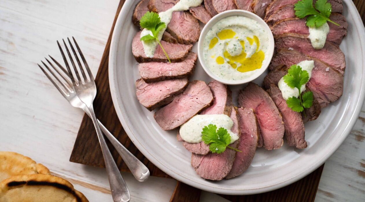 Slices of meat on round plate with a pot of white sauce in the middle, forks and toasted round flat bread on wooden board at one corner.