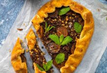 A free form pie with brown meat filling topped with greem leaves on paper on blue top.